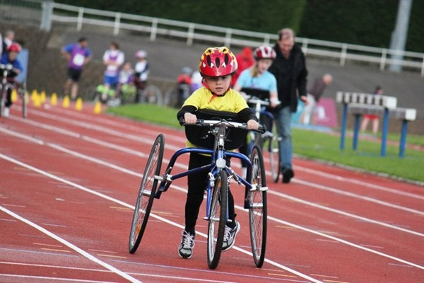 En ung (barn ca 7-8 år) racerunner springer på en utomhusbana.